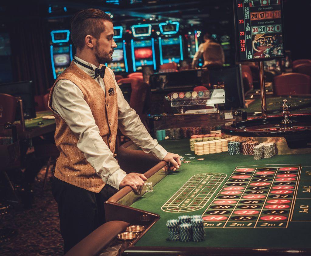 Croupier (dealer) achter een roulettetafel (bron: Envato)