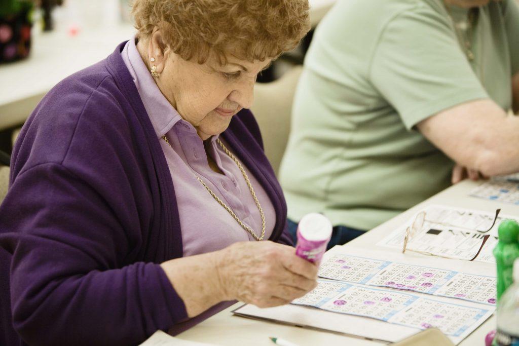Bingo's zijn nog altijd populair in bejaardentehuizen (bron: https://picspree.com/nl/photos/woman-playing-bingo-1239040)