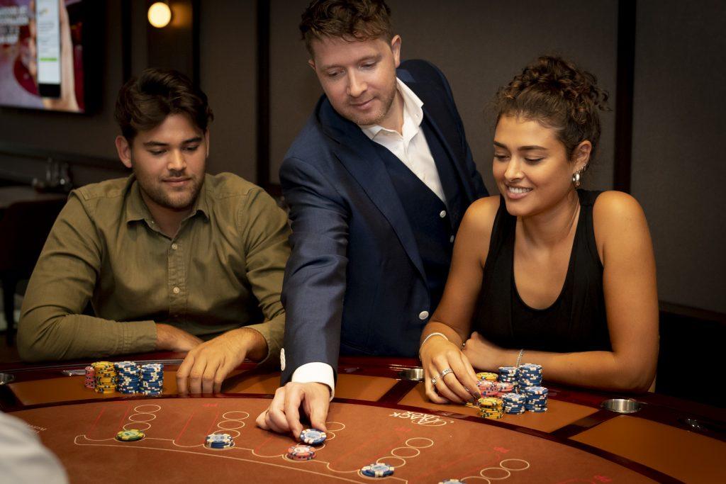 Holland Casino Blackjack black jack speler speelt mee op box van een andere speler