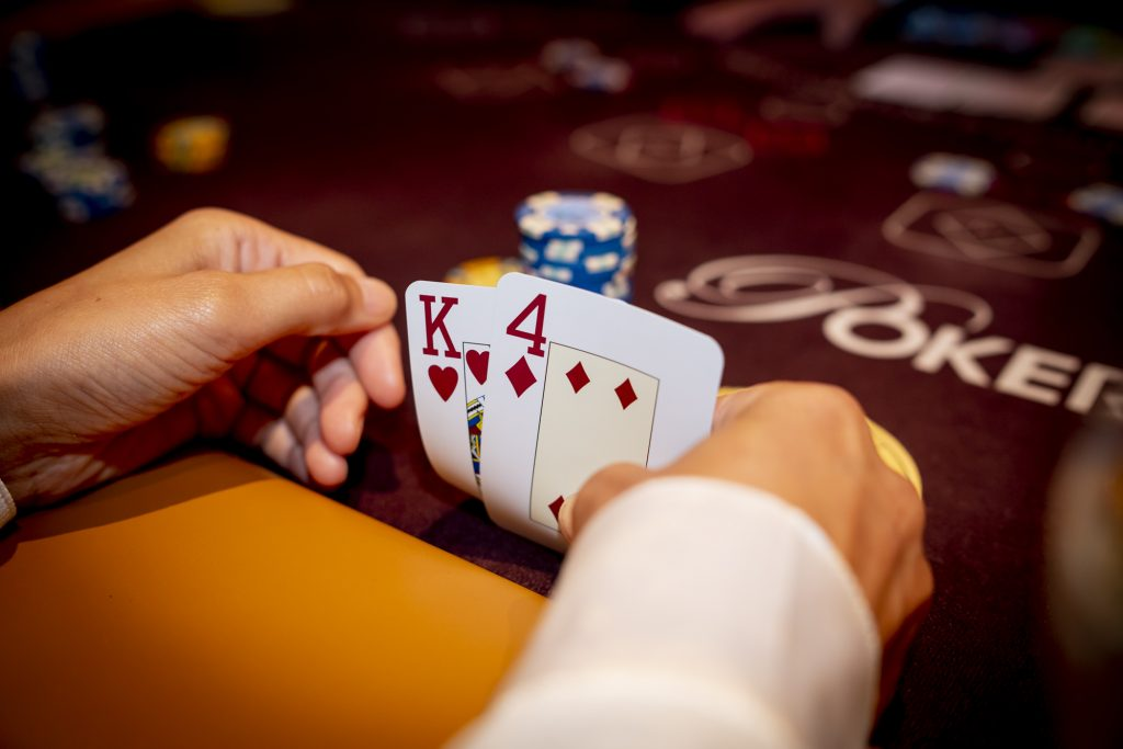 Holland Casino Ultimate Texas Hold'em flop speler bekijkt kaarten K4 4K koning-vier