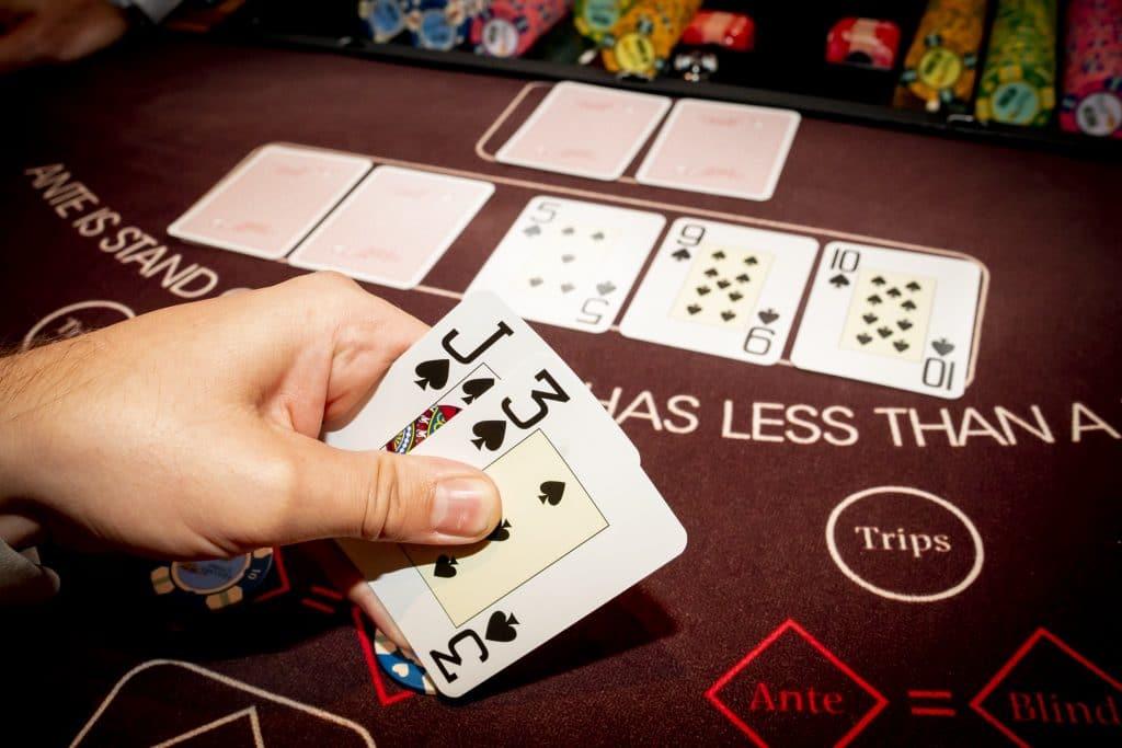 Holland Casino Ultimate Texas Hold'em speler bekijkt kaarten geflopte flush J3