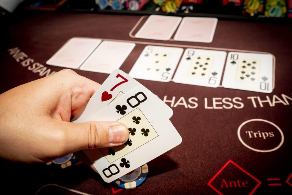 Holland Casino Ultimate Texas Hold'em speler bekijkt kaarten open-ended straight draw straat kans