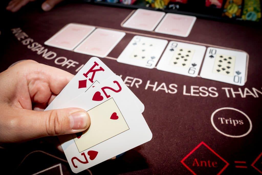 Holland Casino Ultimate Texas Hold'em speler bekijkt kaarten koning-twee K2